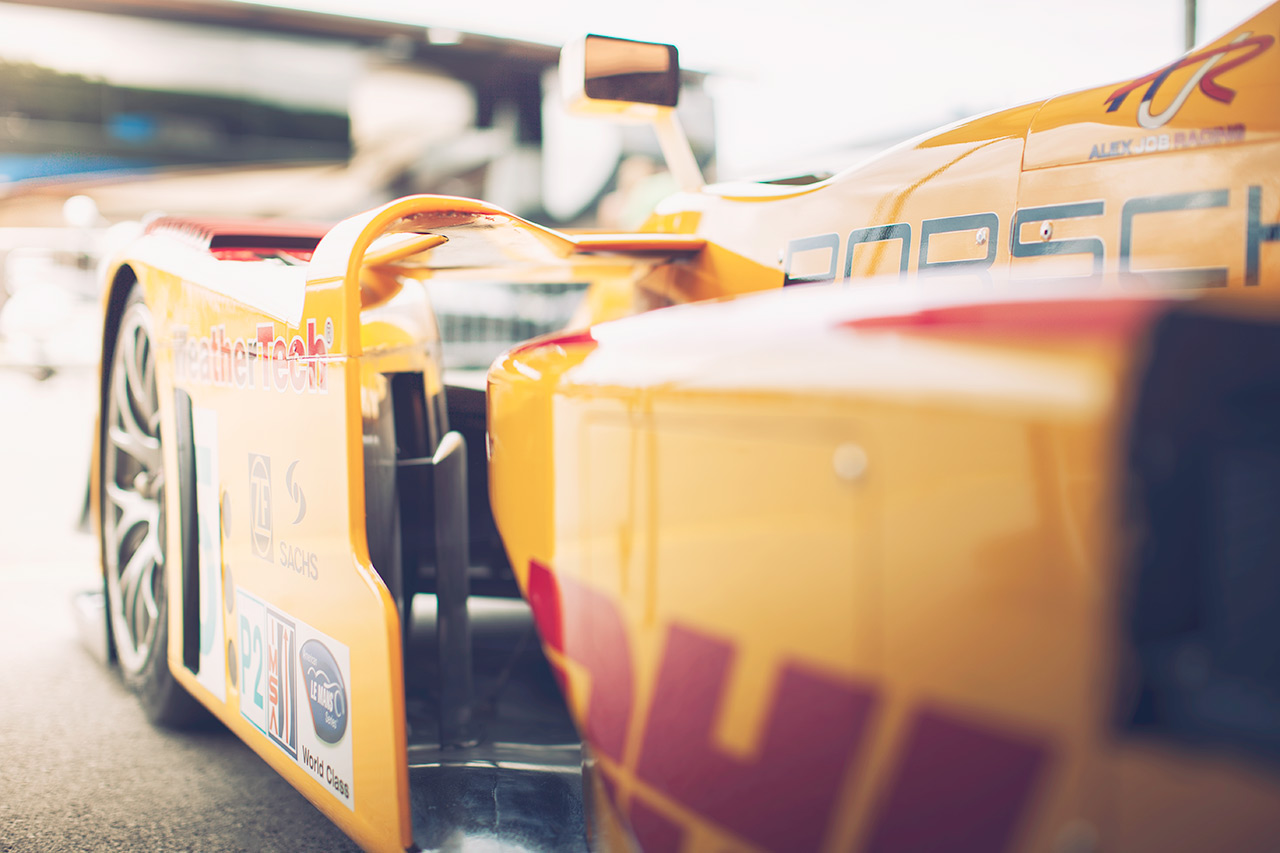 Porsche RS Spyder P2 race car wrapped in DHL livery resting in the paddock between stints