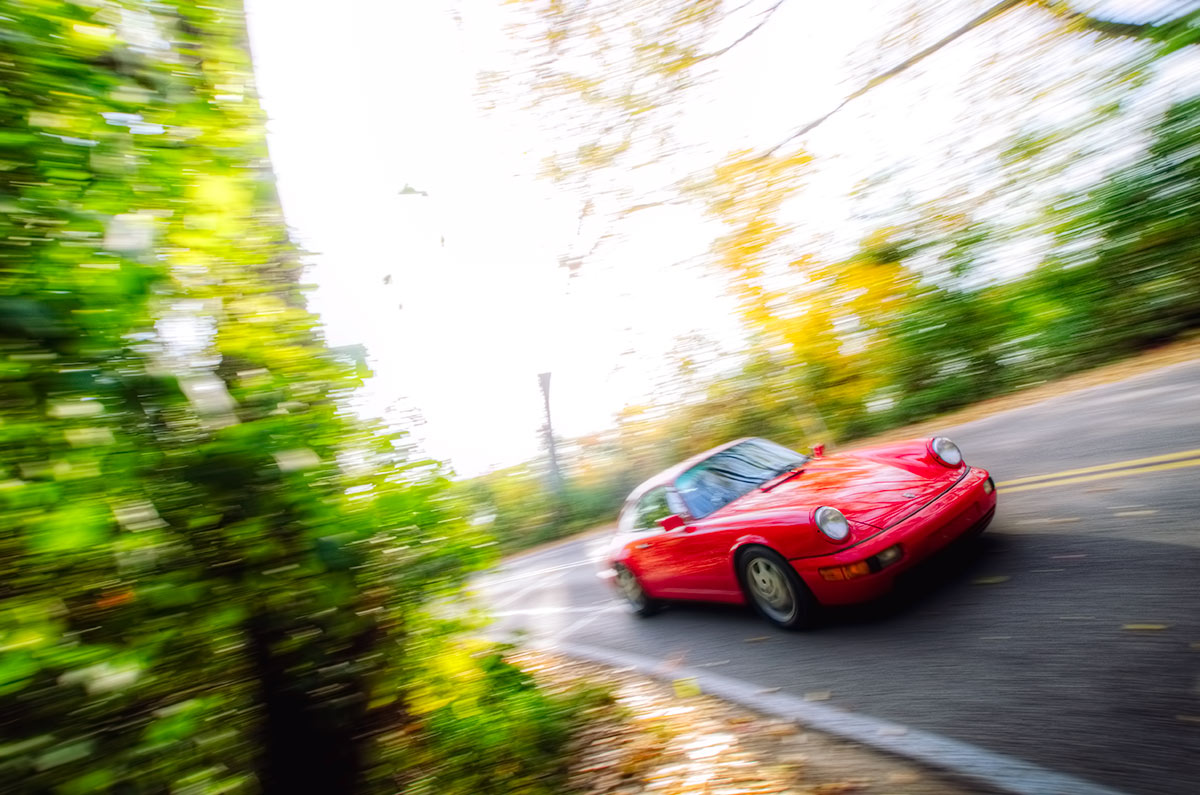 Red Porsche 911 (964) Carrera 4 Emerging from the woods