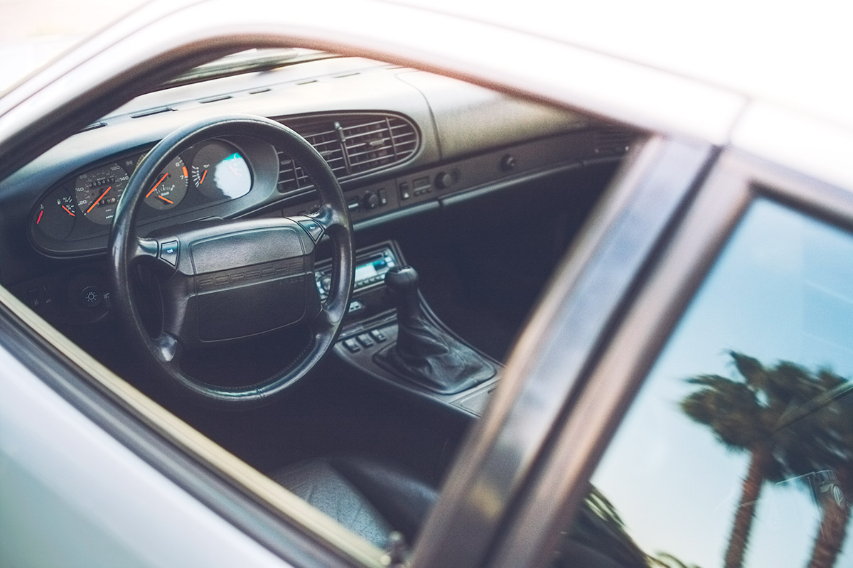 White 1987 Porsche 951interior and palm tree reflection