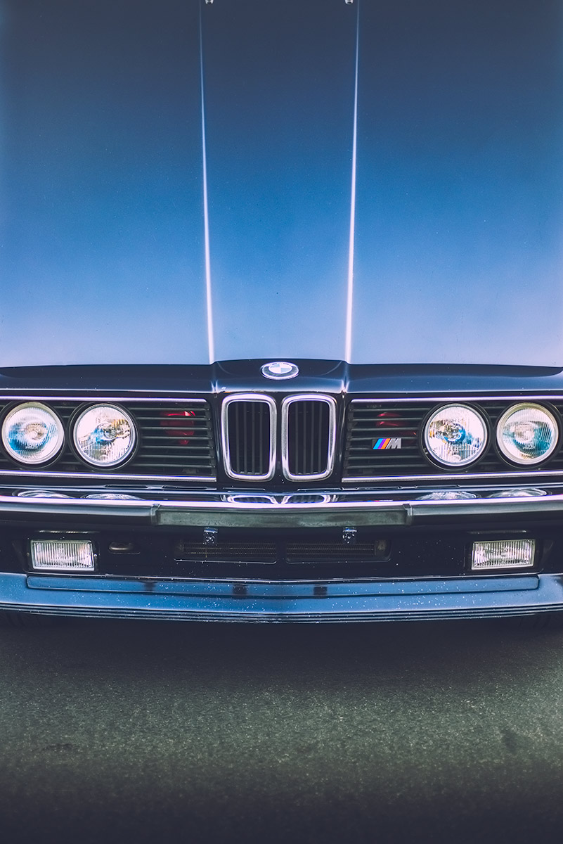 Morning light reflecting off the open hood of an 80s BMW e24 M6