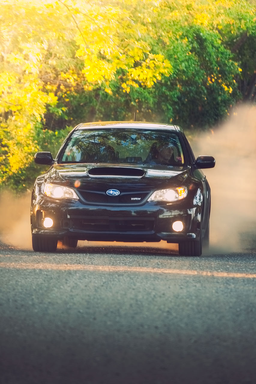 Black 5 Door Subaru WRX at home on a rural loose surface kicking up dust