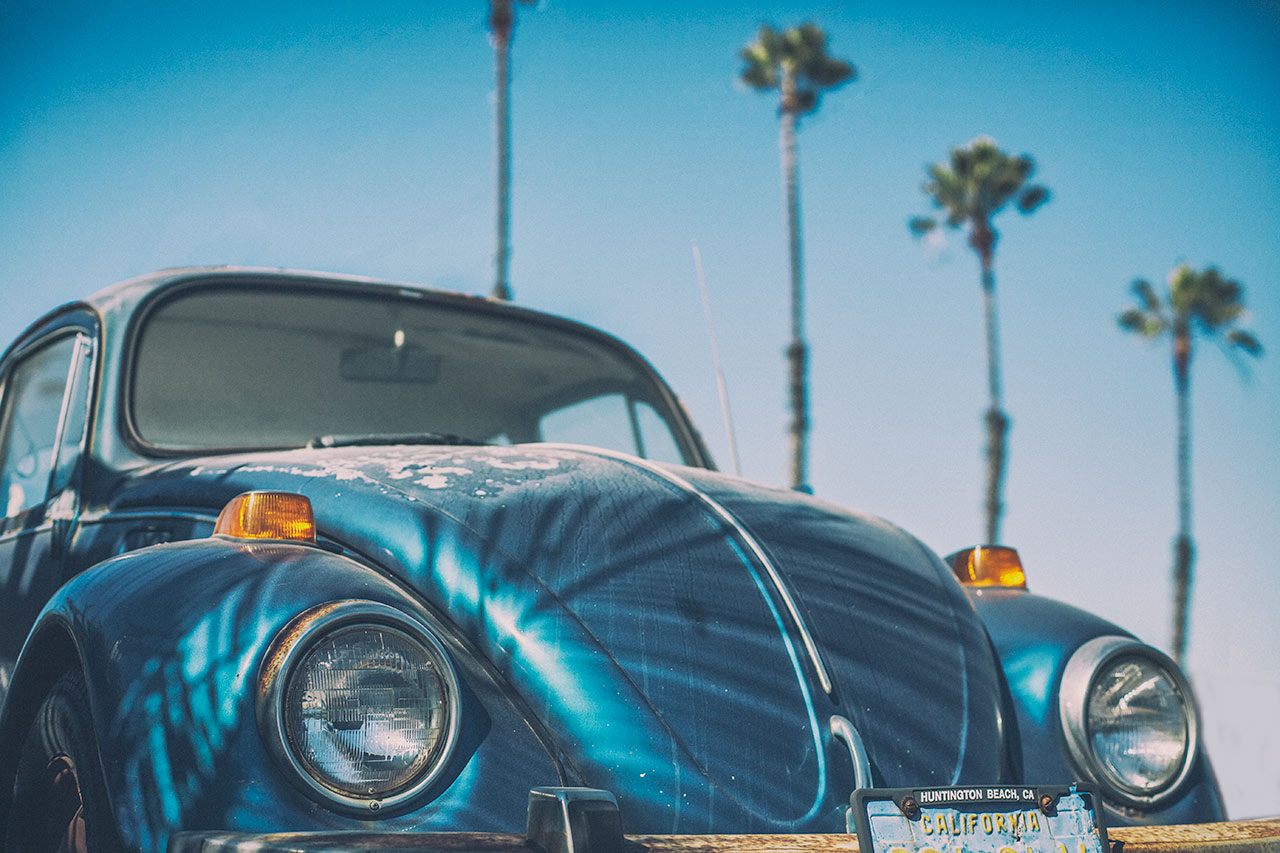 Vintage Volkswagen Beetle surrounded by palm trees in Newport Beach California